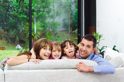 Beautiful hispanic family of four posing with. Heads sticking up from back of sofa looking at camera smiling Stock Photo