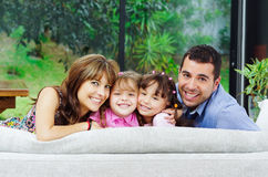 Beautiful hispanic family of four posing with. Heads sticking up from back of sofa looking at camera smiling Royalty Free Stock Photography