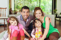 Beautiful hispanic family of four sitting on floor. Of livingroom posing happily for camera Royalty Free Stock Photo