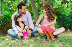 Beautiful hispanic family of four sitting outside. On grass engaging in conversations while posing naturally and happily Stock Photo