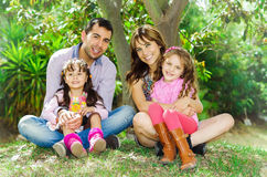 Beautiful hispanic family of four sitting outside. On grass engaging in conversations while posing naturally and happily Royalty Free Stock Photo