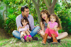 Beautiful hispanic family of four sitting outside. On grass engaging in conversations while posing naturally and happily Royalty Free Stock Photography