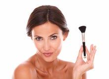 Beautiful hispanic female with make up brush Stock Images