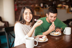 Beautiful Hispanic girl on a date. Portrait of a gorgeous young Hispanic women enjoying some coffee and pie on a date at a cafe Stock Image