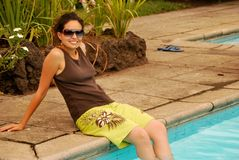 Beautiful Hispanic Girl by the pool. A young, beautiful Hispanic girl sitting by the pool, wearing sunglasses Stock Image