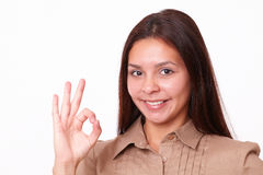 Beautiful hispanic lady with ok gesture. Closeup portrait of beautiful hispanic lady on brown blouse with ok gesture looking at you on isolated studio royalty free stock images
