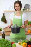 Beautiful  Hispanic or latin american woman is holding wooden spoon while cooking soup  in the kitchen. Beautiful  Hispanic or latin american woman is holding Royalty Free Stock Photo