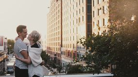 Beautiful Hispanic man and Caucasian woman standing and hugging, holding hands on New York City summer sunset bridge. stock footage