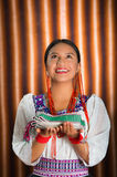 Beautiful hispanic model wearing andean traditional clothing smiling and holding folded textile in hands, posing for. Camera, beige studio curtain background Stock Image