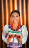 Beautiful hispanic model wearing andean traditional clothing smiling and holding folded textile in hands, posing for. Camera, beige studio curtain background Royalty Free Stock Photo