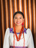 Beautiful hispanic model wearing andean traditional clothing smiling and posing for camera, beige studio curtain Stock Image