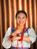 Beautiful hispanic model wearing andean traditional clothing smiling and posing for camera, beige studio curtain Stock Photography