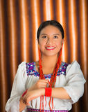 Beautiful hispanic model wearing andean traditional clothing smiling and posing for camera, beige studio curtain Royalty Free Stock Image