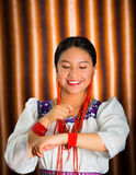 Beautiful hispanic model wearing andean traditional clothing smiling and posing for camera, beige studio curtain Stock Photo