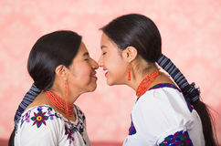 Beautiful hispanic mother and daughter wearing traditional andean clothing, seen from profile angle facing each other Royalty Free Stock Photography