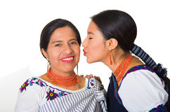 Beautiful hispanic mother and daughter wearing traditional andean clothing, young woman kissing her mom on cheek while Royalty Free Stock Photos