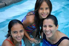Beautiful Hispanic Mother and Daughters. Together in a pool Stock Photos