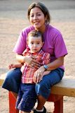 Beautiful Hispanic Mother and son. Sitting outside on a bench Stock Photos