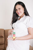 Beautiful hispanic pregnant woman having the word boy with woode Stock Photography