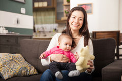 Beautiful Hispanic single mom and her daughter. Cute young Hispanic brunette playing with her baby daughter and a teddy bear at home Royalty Free Stock Photography