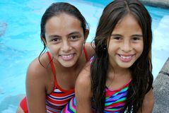 Beautiful Hispanic sisters by the pool. Beautiful Hispanic sisters wearing colorful bathing suits by the pool Stock Images