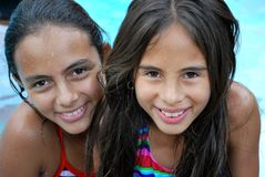 Beautiful Hispanic sisters by the pool. Beautiful Hispanic sisters wearing colorful bathing suits by the pool Stock Photography