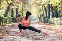 Beautiful hispanic sport woman in sportswear stretching body next smiling happy doing flexibility exercises Royalty Free Stock Photos