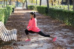 Beautiful hispanic sport woman in sportswear stretching leg on bench doing flexibility exercises warm up before running. Young attractive and beautiful hispanic Stock Photos