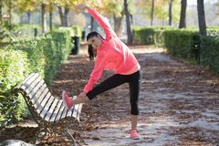 Beautiful hispanic sport woman in sportswear stretching leg on bench doing flexibility exercises warm up before running. Young attractive and beautiful hispanic Royalty Free Stock Image