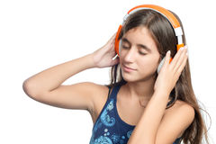 Beautiful hispanic teenage girl enjoying music on bright orange headphones Royalty Free Stock Image