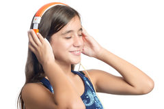 Beautiful hispanic teenage girl enjoying music on bright orange headphones Stock Image