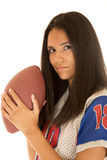 Beautiful Hispanic teenage girl holding an American football Stock Photo