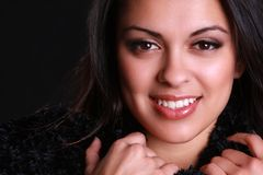 Beautiful hispanic woman. A beautiful hispanic woman with a pretty smile clutching her scarf stock photography