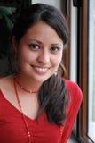 Beautiful Hispanic woman. A Young Smiling Hispanic Woman by a window Royalty Free Stock Image