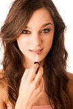 Beautiful hispanic woman aplying lip gloss Stock Photography
