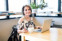 Beautiful hispanic woman at cafe with laptop. Portrait of beautiful middle aged hispanic woman sitting at coffee shop with laptop in table stock photography