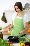 Beautiful Hispanic woman cooking in kitchen. Girl frying in a skillet something. Healthy meal and householding concepts.  royalty free stock photography
