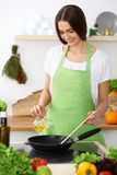Beautiful Hispanic woman cooking in kitchen. Girl frying in a skillet something. Healthy meal and householding concepts.  royalty free stock photos