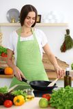 Beautiful Hispanic woman cooking in kitchen. Girl frying in a skillet something. Healthy meal and householding concepts.  stock photography