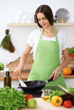 Beautiful Hispanic woman is cooking in the kitchen Stock Photos