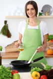Beautiful Hispanic woman is cooking in the kitchen Stock Image