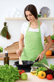 Beautiful Hispanic woman is cooking in the kitchen Royalty Free Stock Photography