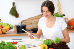 Beautiful  Hispanic woman is cooking in the kitchen. Housewife is tasting fresh salad while sitting at the table Stock Photography
