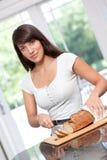 Beautiful hispanic woman cutting bread. Beautiful young hispanic woman cutting bread Royalty Free Stock Photo