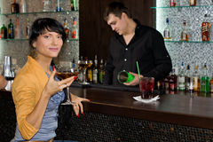 Beautiful Hispanic woman drinking at the bar royalty free stock photography