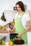 Beautiful Hispanic woman in a green apron cooking in the kitchen Royalty Free Stock Image