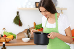 Beautiful Hispanic woman in a green apron cooking in the kitchen Stock Photography