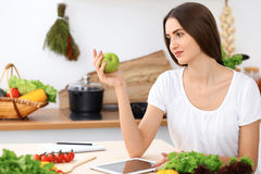 Beautiful Hispanic  woman is keeping green apple while searching internet for a new recipe Stock Photography