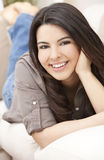 Beautiful Hispanic Woman Laying on Sofa Smiling Royalty Free Stock Image