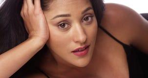 Beautiful Hispanic woman lying on bed royalty free stock photography